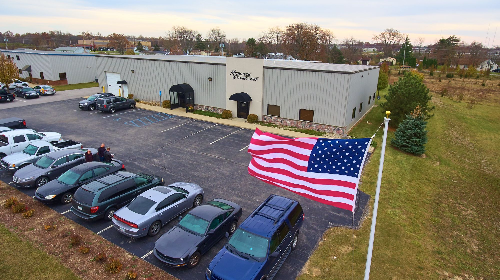 Outside the Fort Wayne Microtech facility with American Flag waving in the breeze